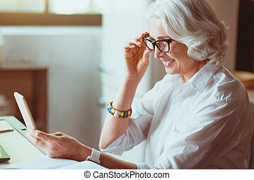 Positive senior woman using smart phone