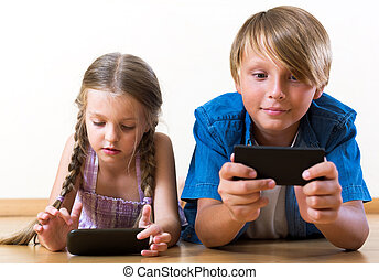 Positive siblings playing with phones - Portrait cheerful ...
