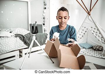Positive smart boy taking a dinosaur skull model form the box