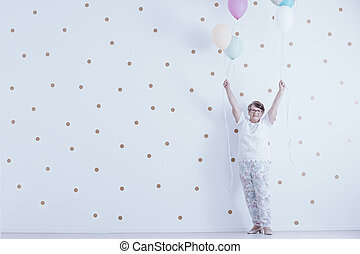 Positive smiling elderly woman with colorful balloons against white wall with gold dots