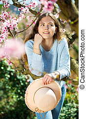 Positive smiling girl posing in blooming garden