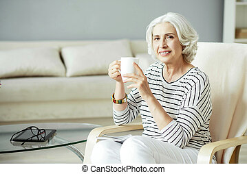 Positive smiling woman drinking tea