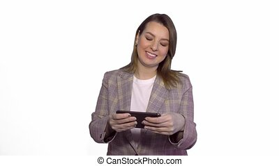 Positive smiling young woman playing games on mobile phone isolated over white background