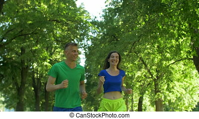 Positive sport runners jogging on park trail