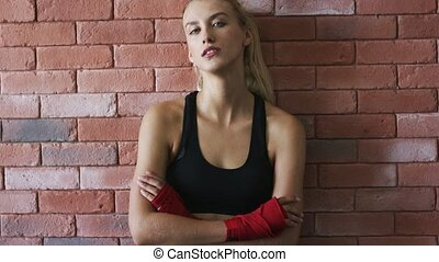 Positive sportswoman leaning on brick wall - Pretty young...