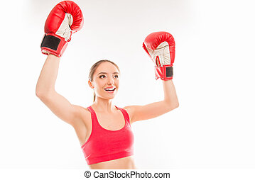 Positive sporty girl in boxing gloves raised her hands up and triumphing