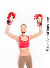 Positive sporty girl in boxing gloves triumphing