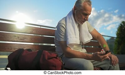 Positive sporty man resting on the bench