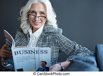 Positive stylish old woman is enjoying periodical in office...