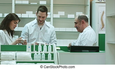 Positive team of pharmacists looking at box of tablet at the hospital pharmacy