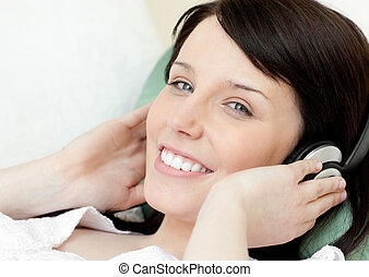 Positive teen girl listening music lying on a sofa