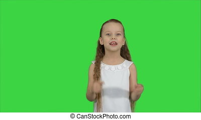 Positive teen girl talking to a camera with a smile on a Green Screen, Chroma Key