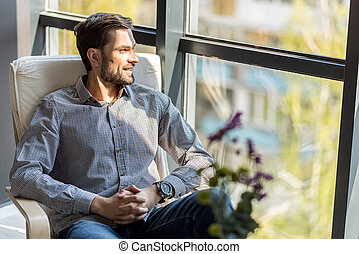 Positive thoughtful guy resting with comfort
