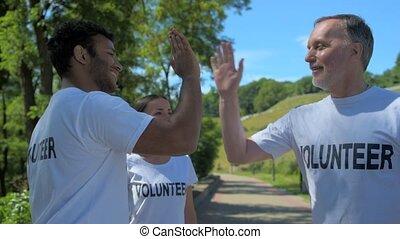 Positive volunteers giving high five - Good job. Cheerful...