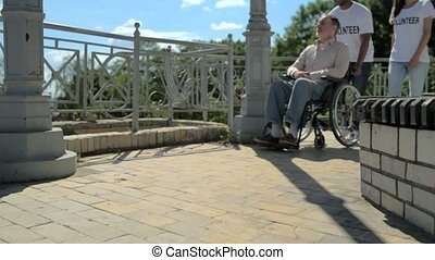 Positive wheelchaired man walking with a helpful volunteers