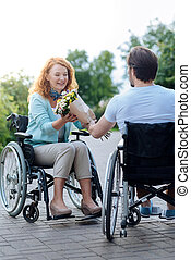 Positive wheelchaired woman getting flowers from her caring disabled husband