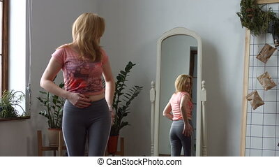 Positive woman admiring her body shape in mirror