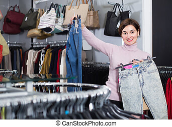 Positive woman deciding on new jeans