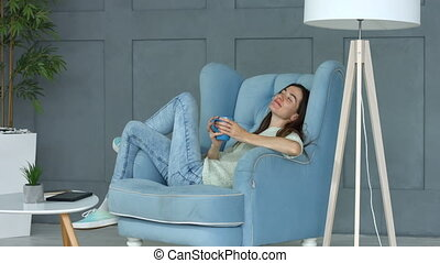 Positive woman enjoying morning coffee in armchair
