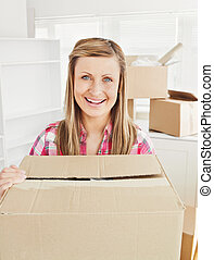 Positive woman holding a box standing in her new house looking at the camera after moving