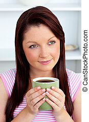 Positive woman holding a cup of coffee at home