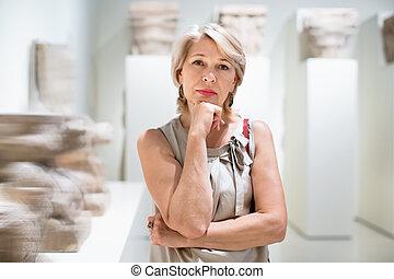 Positive woman in art museum near the antique classical sculpture