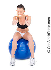 Positive woman in sportswear sitting on exercise ball giving thumbs up to camera on white background