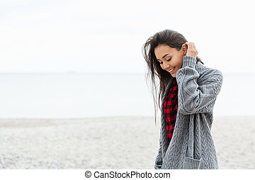 Positive woman looking down while walking on beach