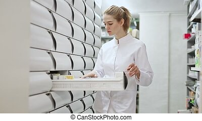 Positive woman pharmacist browsing rows of drugs in pharmacy...