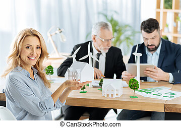 Positive woman showing a model of a house while sitting with colleagues