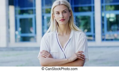 Positive woman standing near building - Attractive young...