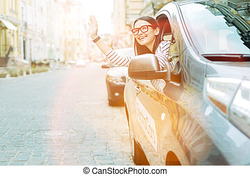 Positive woman waving to the passersby