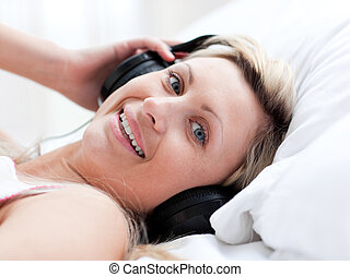 Positive woman with headphones on lying on a bed