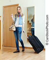positive woman with luggage  in home