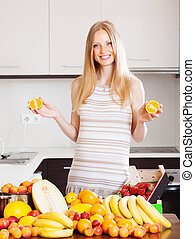 Positive woman with oranges and other fruits