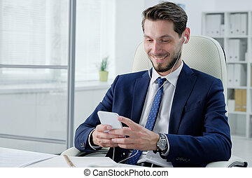 Positive young businessman checking phone