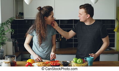 positive young caucasian couple listening to music on smartphone dancing, woman cutting red pepper and giving to try her husband, then man gives her to try a piece of pepper