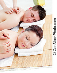 Positive young couple receiving a back massage