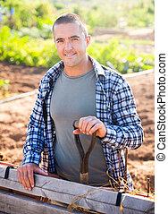 Positive young gardener posing in vegetable garden