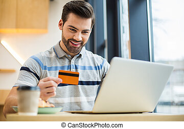 Positive young man making an online payment