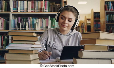 Positive young smiling woman in white headphones is sitting at table in university library holding digital tablet and listening to music. She is dancing a bit and writing lecture in notebook