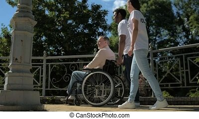 Positive young volunteers helping a wheelchaired man
