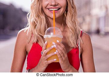 Positive young woman enjoying her orange juice