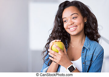 Positive young woman holding an apple.
