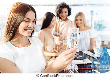 Positive young woman looking at her glass
