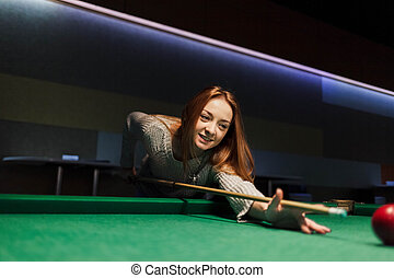 Positive young woman plays billiards in a dark club