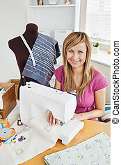 Positive young woman sewing clothes at home in the kitchen