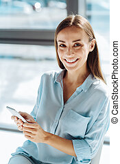 Positive young woman using her smart phone