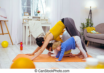 Positive young woman working out with her children