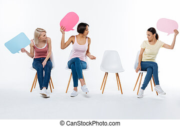 Positive young women looking at the chair